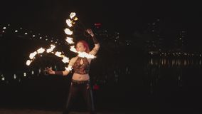 Artist creating fire circle spinning fans at dusk stock footage