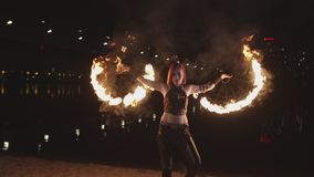 Skillful firegirl spinning burning fans by river stock footage