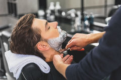 Skillful hairdresser using blade for shaving beard Royalty Free Stock Photos