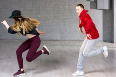 Skillful hip-hop dancers in movement. Young couple of modern dance dancing on studio background Royalty Free Stock Image