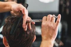 Skillful male barber doing haircut Stock Photo