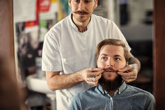 Skillful male barber is serving his client. Mustache Royalty Free Stock Images