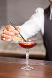 Skillful male bartender is preparing drink in pub. Close up of hand of barman mixing cocktail with tubule in bar. He is standing in uniform Royalty Free Stock Photos