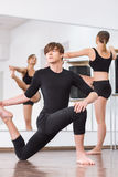 Skillful male dancer having a dance training. Involved in the workout. Skillful handsome young men sitting on the floor and holding his leg while focusing on his Royalty Free Stock Images