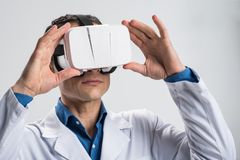 Skillful male doctor fitting VR glasses. Virtual world.  Appealing attractive male doctor putting on VR glasses while standing on the isolated background and Royalty Free Stock Photo