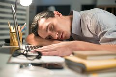 Skillful male employee falling asleep during work. A minute sleep. Appealing cute male employee seeing dreams while resting on the table where laptop standing Stock Images