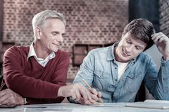 Skillful male engineers finishing blueprint. Help from mentor. Two appealing professional male engineers working on blueprint while smiling and posing at table Stock Photo