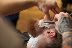 Skillful male hairdresser is serving his client Stock Images