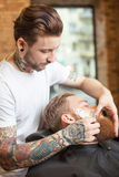 Skillful male hairdresser is serving his customer Royalty Free Stock Photos
