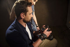 Skillful male photographer watching shots with woman Royalty Free Stock Images