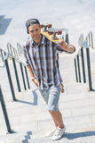Skillful male skateboarder resting outdoors. Happy young man is carrying skateboard on his shoulder. He is standing on steps and keeping hand in pocket. Guy is Stock Image