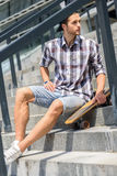 Skillful male skateboarder resting on steps. Confident young man is waiting for someone on staircase. He is sitting and holding skateboard. Skater is looking Royalty Free Stock Photo