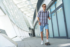 Skillful male skater entertaining near building. Joyful young man is riding skateboard and smiling Stock Images