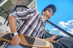 Skillful male skater relaxing on staircase. Low angle of pensive young man sitting on stairs with skateboard. He is listening to music from earphones and holding Royalty Free Stock Images