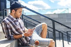 Skillful male skater using smartphone. Cool young man is messaging on mobile phone with concentration. He is sitting on stairs near skate and relaxing Stock Photos