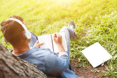Skillful male student is making some notes. Cute young man is writing in notebook with inspiration. He is sitting on grass near tree in park. The guy is Stock Photo