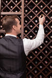 Skillful male waiter is working in winehouse. Professional young sommelier is choosing a bottle of wine in a cellar. He is standing in a tuxedo. The man is Stock Images