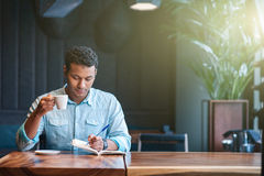Skillful male worker is drinking hot beverage Royalty Free Stock Photo