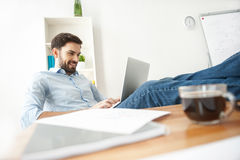 Skillful male worker is using a notebook. Handsome young man is typing on laptop in office. He is sitting and relaxing. Man is smiling. Documents and cup of Royalty Free Stock Images
