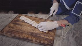 Skillful man in blue chef uniform cooking kebab in modern turkish restaurant. Cook cuts kebab wrapped in pita lavash. With big sharp knife in pieces close up stock footage