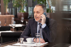 Skillful mature manager is using telephone for communication Royalty Free Stock Photography