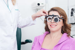 Skillful ophthalmologist with equipment for lens determination Stock Photos