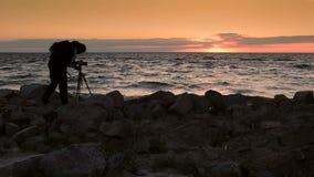 Skillful photograper shooting sea in twilight time stock video