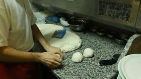 Skillful pizzaiolo preparing balls of dough for pizza, traditional Italian dish stock video