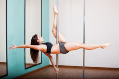 Skillful pole dancer working out Royalty Free Stock Images