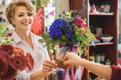 Skillful saleswoman getting payment for bouquet Stock Photo
