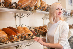 Skillful saleswoman is serving customers in bakery Stock Photos