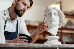 Free Skillful Sculptor Makes Professional Restauration Of Gypsum Sculpture Of Woman`s Head At The Creative Workshop. Stock Image - 168936971