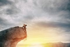 Businessman on the peak of a mountain to find new business stock photo