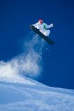 Skillful snowboarder. Photo of brave sportsman jumping on snowboard over blue sky Stock Images