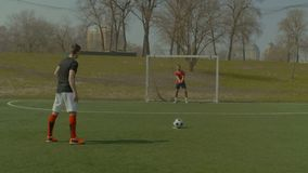 Skillful soccer goalie making penalty save. Skillful young soccer goalkeeper making penalty save during football match. Striker taking penalty kick and goalie stock video footage
