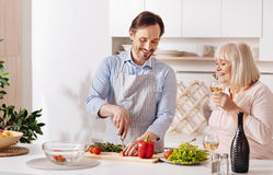 Skillful son helping aged mother in the kitchen. Expressing care to my mom. Charming positive skilled son standing in the kitchen and cooking vegetable salad Royalty Free Stock Images