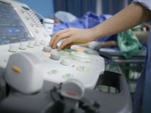Skillful sonographer using ultrasound machine at work. In clinic/hospital for diagnosis Royalty Free Stock Images