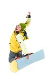 Skillful teenager. Image of courageous guy jumping on snowboard in the air Royalty Free Stock Photos