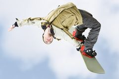 Skillful teenager. Image of courageous guy jumping on snowboarder in the air Royalty Free Stock Photography
