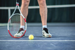 Skillful tennis player standing near equipment Royalty Free Stock Image