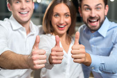Skillful three office managers are working as a team. Cheerful young businessmen and businesswoman are giving thumbs up. They are looking at camera and laughing Royalty Free Stock Images