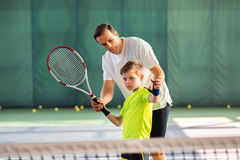 Skillful trainer teaching kid holding racquet. Professional male tennis player is explaining to child how to play tennis. He is adjusting racket in childish Royalty Free Stock Photography