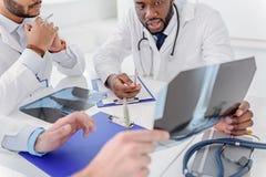 Skillful traumatologists discussing radiograph of human leg Stock Photo