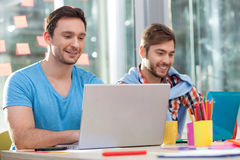 Skillful two male workers are using notebook royalty free stock image