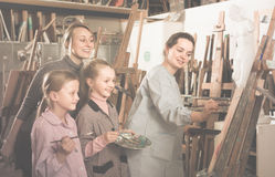 Skillful woman teacher showing her skills during painting class. Skillful young germany women teacher showing her skills during painting class at art studio Stock Image