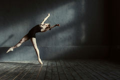 Skillful young ballet dancer acting in the black colored room Royalty Free Stock Images