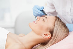 Skillful young cosmetologist is treating her Royalty Free Stock Image