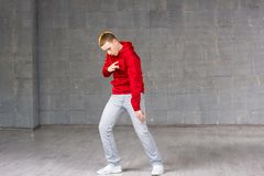 Skillful young dancer in movement. Young modern style male dancer performing hip-hop dance on studio background. Stylish and talented caucasian dancer boy Royalty Free Stock Photography