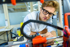 Skillful young engineer constructing 3d printing Stock Photo