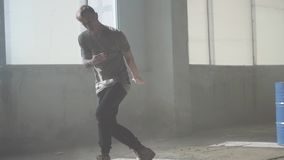 Skillful young passionate hip-hop dancer performing in front of camera. The man stretches his arms forward, then makes. Portrait of young passionate hip-hop stock footage